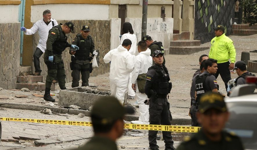 CORRECTS TO TWO DOZEN POLICE OFFICERS INJURED AND NO DEATHS - Police and investigators inspect the site where a homemade bomb exploded near the Santamaria bull ring in Bogota, Colombia, Sunday, Feb. 19, 2017. The artefact was detonated just a few hours before a scheduled bullfight, as police in riot gear were congregating ahead of a demonstration by animal rights activists. An official police statement said that 26 people suffered shrapnel and blast injuries, all but two of them officers. (AP Photo/Ricardo Mazalan)