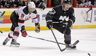 New York Islanders center Casey Cizikas (53) and New Jersey Devils left wing Taylor Hall (9) go after a loose puck during the first period of an NHL hockey game, Sunday, Feb. 19, 2017, in New York, (AP Photo/Kathy Willens)