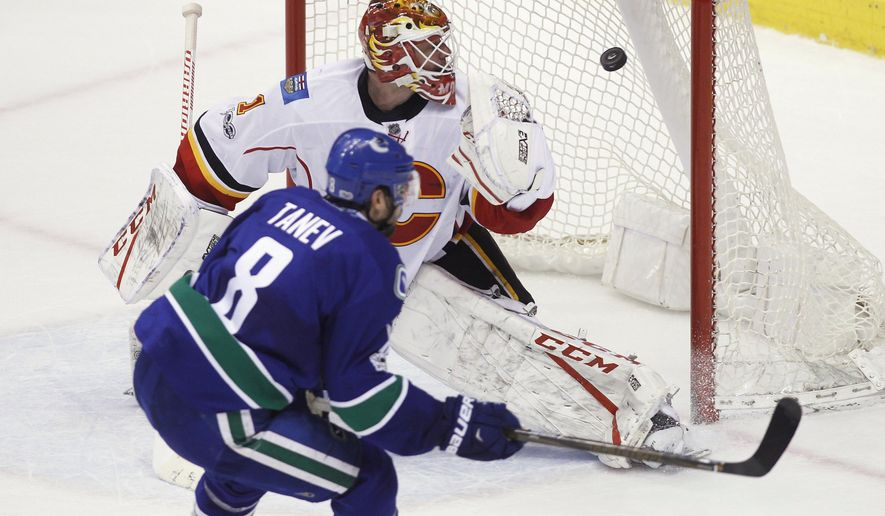 Vancouver Canucks defenseman Christopher Tanev (8) scores the game-winning goal against Calgary Flames goalie Brian Elliott (1)  during overtime of an NHL hockey game Saturday, Feb. 18, 2017, in Vancouver, British Columbia. (Ben Nelms/The Canadian Press via AP)