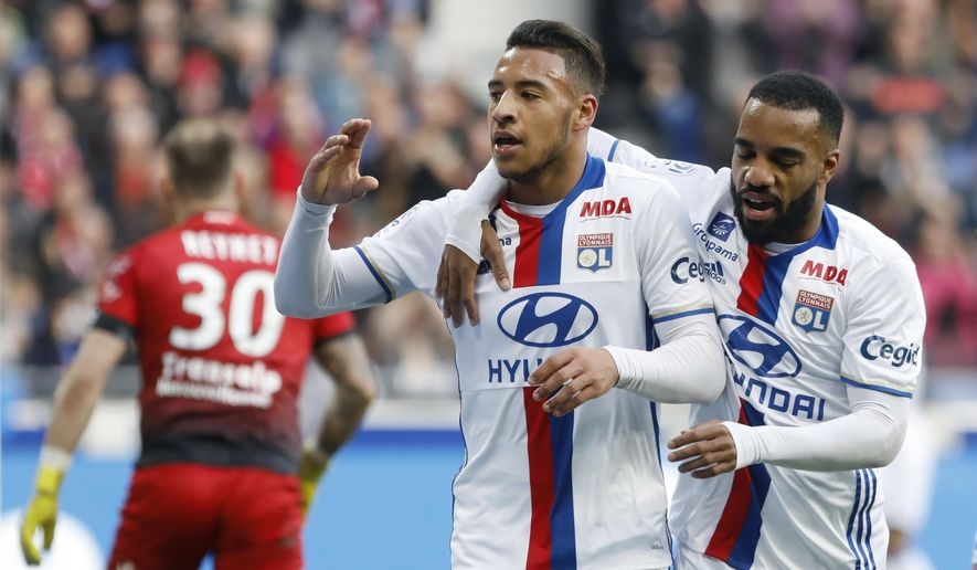 Lyon's Corentin Tolisso, center, celebrates with Alexandre Lacazette, right, after he scored a goal against Dijon during their French League One soccer match in Decines, near Lyon, central France, Sunday, Feb. 19, 2017. (AP Photo/Laurent Cipriani)