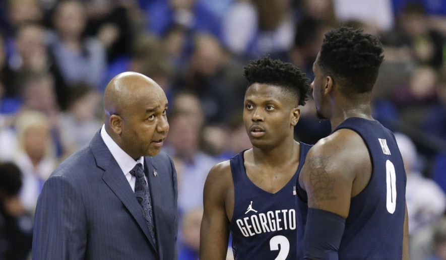 Georgetown coach John Thompson III talks to Jonathan Mulmore (2) and L.J. Peak (0) during the first half of an NCAA college basketball game in Omaha, Neb., Sunday, Feb. 19, 2017. (AP Photo/Nati Harnik) **FILE**