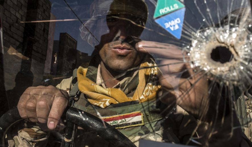 FILE -- In this Dec. 6, 2016  file photo, an Iraqi soldier of the 9th division is seen within a Humvee in Shyma district in Mosul, Iraq. Iraqi forces, backed by the U.S.-led international coalition, launched a campaign in October to retake Mosul, the country's second largest city and IS's last major urban bastion in Iraq. (AP Photo/Manu Brabo, File)