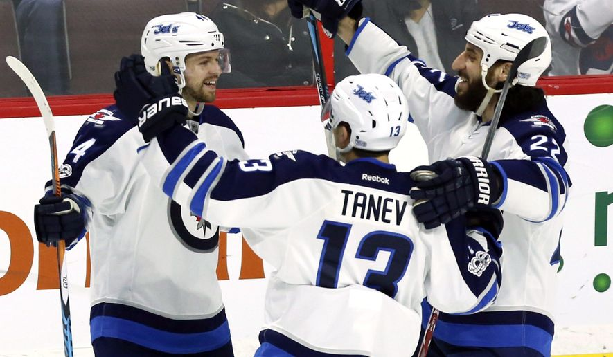 Winnipeg Jets' Josh Morrissey (44) celebrates his goal against the Ottawa Senators with teammates Brandon Tanev (13) and Chris Thorburn (22) during third period NHL hockey action in Ottawa, Sunday Feb. 19, 2017. (Fred Chartrand/The Canadian Press via AP)