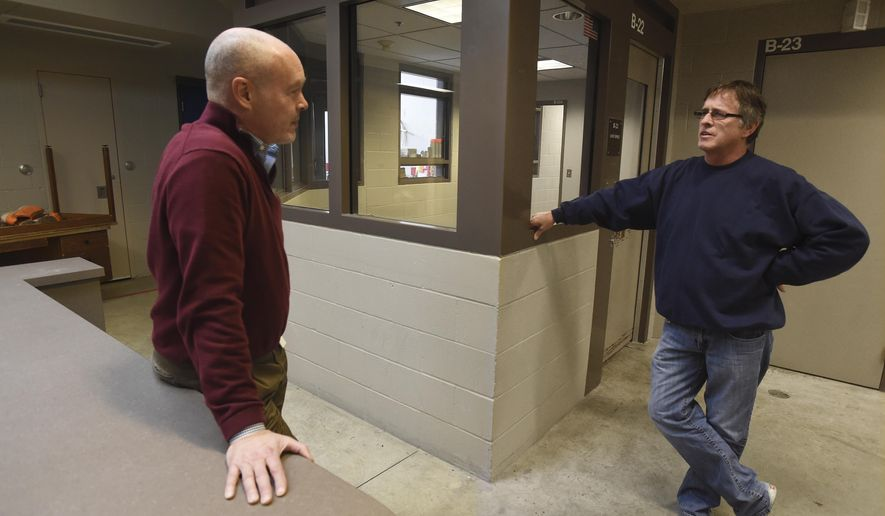 ADVANCE FOR WEEKEND EDITIONS, FEB. 18-19 - In this Feb. 2, 2017 photo, standing in an empty cell wing, Juvenile Court administrator Mike Fenton, left, chats with detention supervisor Chris Marx during a tour of Thurston County's Juvenile Detention Facility in Tumwater, Wash., which has seen massive population decreases in recent years due to changes in how juvenile cases are handled. (Steve Bloom/The Olympian via AP)
