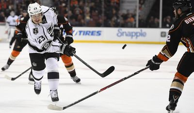 Los Angeles Kings right wing Dustin Brown, left, shoots as Anaheim Ducks defenseman Kevin Bieksa defends during the first period of an NHL hockey game, Sunday, Feb. 19, 2017, in Anaheim, Calif. (AP Photo/Mark J. Terrill)