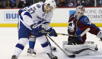 Tampa Bay Lightning left wing Jonathan Drouin, front left, scores the winning goal past Colorado Avalanche goalie Calvin Pickard, right, as Colorado Avalanche left wing Matt Nieto, back left, defends in overtime of an NHL hockey game, Sunday, Feb. 19, 2017, in Denver. Tampa Bay won 3-2. (AP Photo/David Zalubowski)
