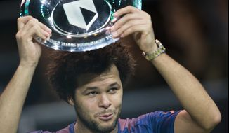 France's Jo-Wilfried Tsonga holds the trophy as he celebrates winning his match against Belgium's David Goffin in three sets, 4-6, 6-4, 6-1, in the men's singles final of the ABN AMRO world tennis tournament at the Ahoy stadium in Rotterdam, Netherlands, Sunday, Feb. 19, 2017. (AP Photo/Peter Dejong)