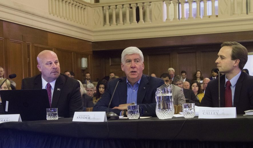 FILE - In a Feb. 8, 2017 file photo, Michgian Gov. Rick Snyder, center, flanked by Budget Director Al Pscholka, left, and Lt. Gov Brian Calley, presents the budget before the joint Senate and House Appropriations Committees in Lansing, Mich. Faced with discouraging test scores, Gov. Rick Snyder is proposing a shift so much more state money is spent on academically at-risk students and less goes toward educating private and home-schooled students or those attending online charter schools. (Dale G. Young/Detroit News via AP, File)
