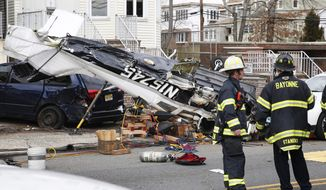 Firefighters stand near wreckage of a small plane that crashed on Sunday, Feb. 19, 2017, in Bayonne, N.J. Authorities said the pilot was pulled from the wreckage, but further details on that person and their injuries were not immediately available. (Ed Murray/NJ Advance Media via AP)