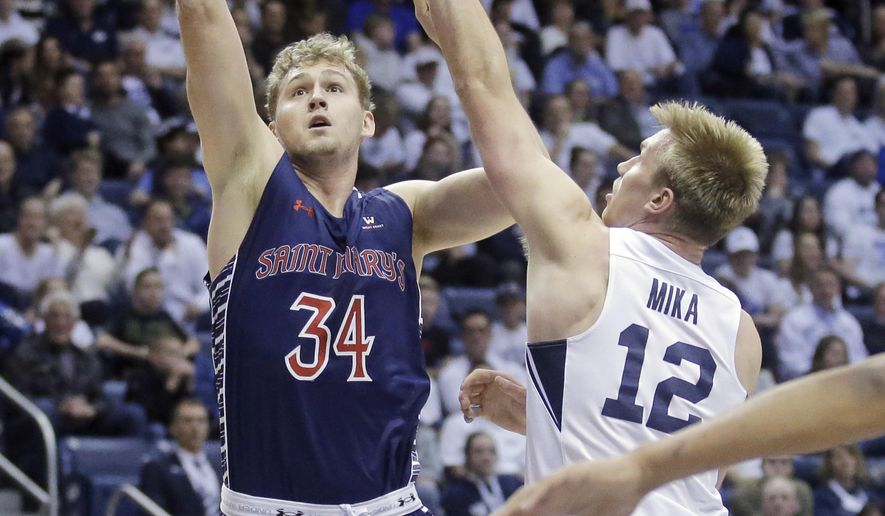 St. Mary's center Jock Landale (34) and shoots as BYU forward Eric Mika (12) defends during the first half of an NCAA college basketball game Saturday, Feb. 18, 2017, in Provo, Utah. (AP Photo/Rick Bowmer)