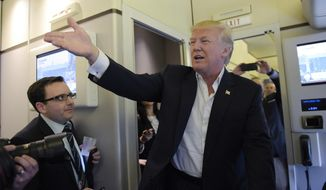 """President Donald Trump talks to reporters on board Air Force One as he arrived to speak at his """"Make America Great Again Rally"""" at Orlando-Melbourne International Airport in Melbourne, Fla., Saturday, Feb. 18, 2017.  (AP Photo/Susan Walsh)"""