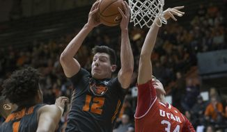 Oregon State's Drew Eubanks (12) grabs a rebound away from Utah's Jayce Johnson (34) during the first half of an NCAA college basketball game in Corvallis, Ore., Sunday, Feb. 19, 2017. (AP Photo/Timothy J. Gonzalez)