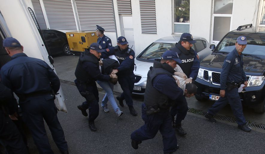 In this Sunday, Oct. 16, 2016, file photo, Montenegrin police officers escort people suspected of planning armed attacks after the parliamentary vote in Podgorica, Montenegro. Montenegro's special prosecutor  Milivoje Katnic, has accused Russia and its secret service operatives of plotting a coup attempt that included plans to kill the small Balkan country's former prime minister, Milo Djukanovic, following an investigation. (AP Photo/Darko Vojinovic, File)