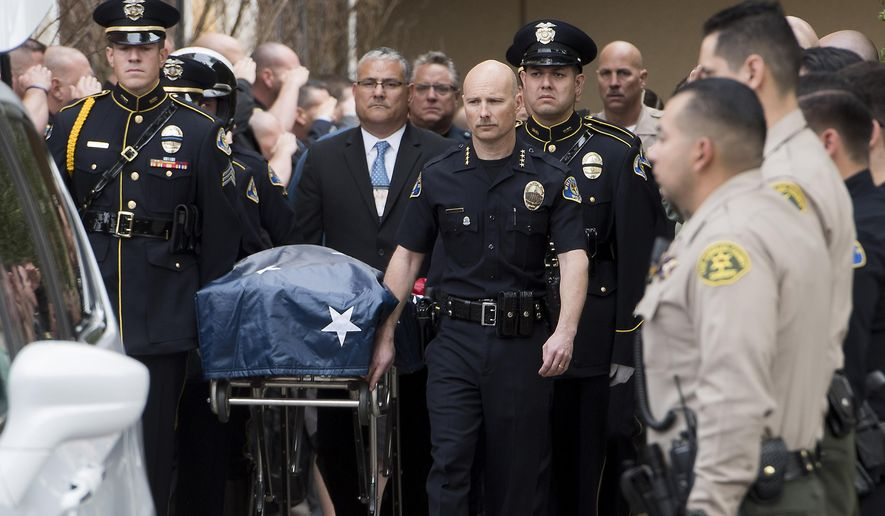 Whittier Police Chief Jeff Piper, center right, along with an honor guard wheel the gurney with a fallen officer's body at UCI Medical Center in Orange, Calif., Monday, Feb. 20, 2017. A California police officer was killed and another wounded in a shooting Monday while they were trying to help a man who had been in a traffic accident in Whittier, officials said. (Sam Gangwer/The Orange County Register via AP)