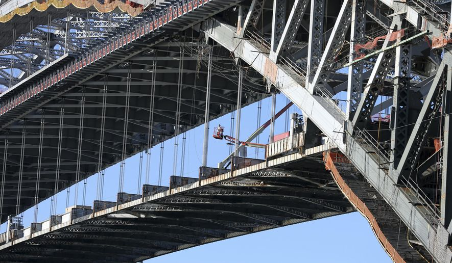 A worker uses a lift as he works below the new roadway on the old road deck on the Bayonne Bridge Monday, Feb. 20, 2017, in Bayonne, N.J. The Port Authority of New York and New Jersey says the bridge connecting Bayonne to New York's Staten Island opened for vehicles on the new upper deck roadway at 5 a.m. Monday after years of work to raise the deck. (AP Photo/Mel Evans)