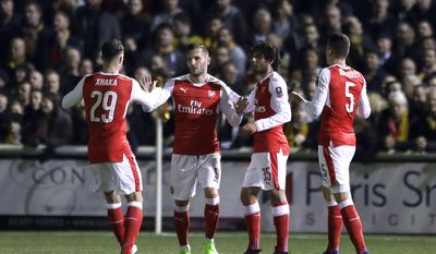 Arsenal's Lucas Perez, second left, is congratulated by teammates Granit Xhaka, left, Alex Oxlade-Chamberlain and Gabriel, right, after scoring a goal during their English FA Cup fifth round soccer match against Sutton United at Gander Green Lane stadium in London, Monday, Feb. 20, 2017. (AP Photo/Matt Dunham)