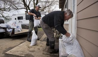 Bill Bernstein and his son Will, lay sandbags around at the door of his home as they prepare for another storm Sunday, Feb. 19, 2017, in Maxwell, Calif. The first outer rain bands from a powerful Pacific storm headed to Northern California on Sunday brought light rain and wind and renewed warnings of possible flooding in the already soggy region. (Paul Kitagaki Jr./The Sacramento Bee via AP)