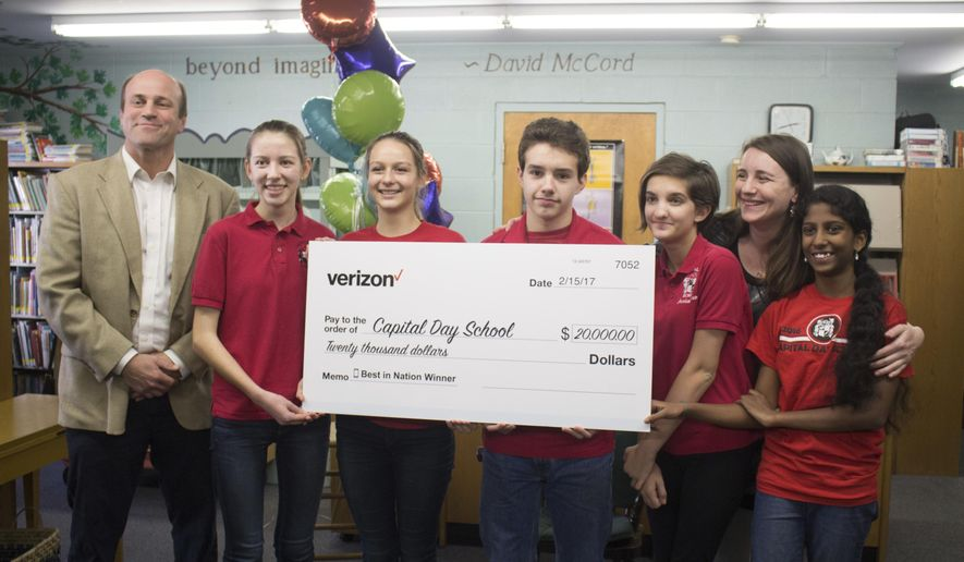 In this Wednesday, Feb. 15, 2017 photo, Capital Day School headmaster Tim Corkran, left, and students, Olivia Moore, Jill Jacobs, Jared Winters, Ana Razavi, teacher Audrey Bebensee and Diksha Satish pose with their $20,000 prize in Frankfort, Ky. The eighth-graders won a national app design competition sponsored by Verizon.  (Alfred Miller/The State Journal via AP)