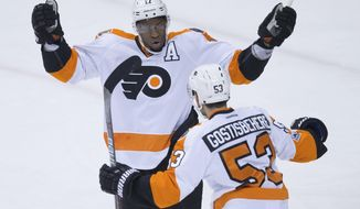 Philadelphia Flyers' Wayne Simmonds, back, and Shayne Gostisbehere celebrate Simmonds' goal against the Vancouver Canucks during the first period of an NHL hockey game in Vancouver, British Columbia, Sunday, Feb. 19, 2017. (Darryl Dyck/The Canadian Press via AP)