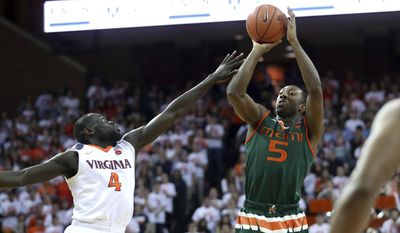 Miami guard Davon Reed (5) shoots over Virginia guard Marial Shayok (4) during the first half of an NCAA college basketball game Monday, Feb. 20, 2017, in Charlottesville, Va. (AP Photo/Ryan M. Kelly)