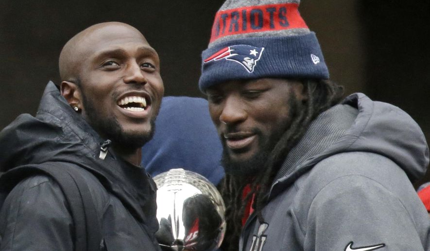 FILE - In this Feb. 7, 2017, file photo, New England Patriots safety Devin McCourty, left, and running back LeGarrette Blount hold a Super Bowl trophy during a rally in Boston to celebrate their win over the Atlanta Falcons in the NFL Super Bowl 51 football game in Houston. McCourty and Blount are among a half-dozen players that have turned down an expected invitation to the White House. (AP Photo/Elise Amendola, File) **FILE**