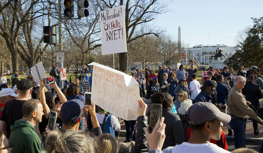 """Marchers stopped at Lafayette Park during their march toward the White House on Monday. The rally was one of several across the country under the banner of """"Not My Presidents Day."""" (Associated Press)"""