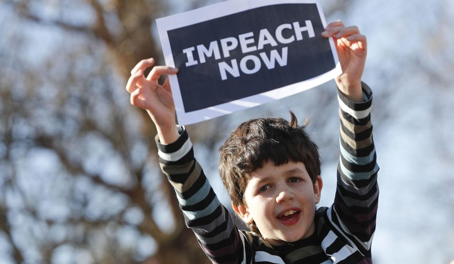 """Marcel Ast, 10, from New Jersey, holds up a sign during a """"Not My Presidents Day"""" rally at DuPont Circle in Washington, Monday, Feb. 20, 2017. Anti-President Donald Trump activists seized on Monday's federal holiday to organize rallies in cities around the country to oppose policies by Trump. (AP Photo/Pablo Martinez Monsivais)"""