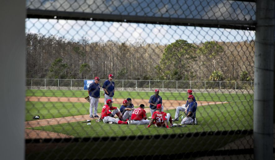Boston Red Sox players sit on the field during a discussion at a spring training baseball workout in Fort Myers, Fla., Sunday, Feb. 19, 2017. (AP Photo/David Goldman)