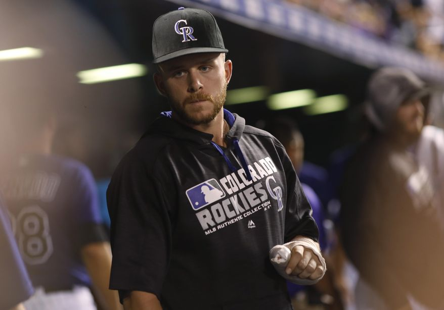 FILE - In this Aug. 8, 2016, file photo, injured Colorado Rockies shortstop Trevor Story talks to teammates in the dugout in the ninth inning of a baseball game against the Texas Rangers in Denver.  From now on, Trevor Story will only slide cleats first. A painful lesson the Rockies shortstop learned last season when he tore a ligament in his left thumb trying to reach his hand into second base. (AP Photo/David Zalubowski, File)