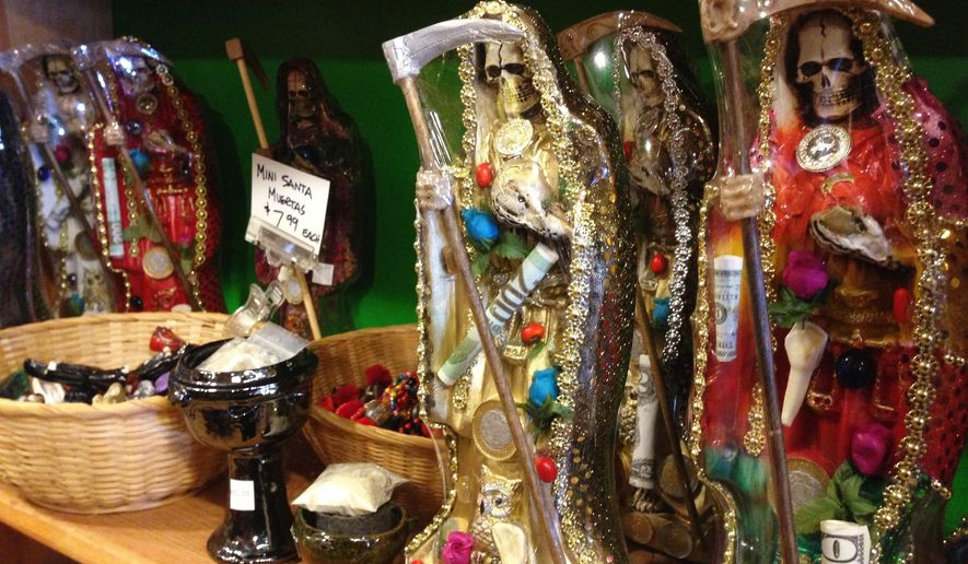 FILE - In this Feb. 13, 2013, file photo, statues of La Santa Muerte are displayed at the Masks y Mas art store in Albuquerque, N.M. Bishops in the United States are finally denouncing the skeleton folk saint known as La Santa Muerte, a figure often connected to the illicit drug trade in Mexico. (AP Photo/Russell Contreras, File)