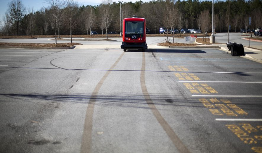 In this Thursday, Jan. 26, 2017 photo, a driverless shuttle bus retraces its tracks while on display at the Riverside EpiCenter in Austell, Ga. Self-driving vehicles could begin tooling down a bustling Atlanta street full of cars, buses, bicyclists and college students, as the city vies with other communities nationwide to test the emerging technology. (AP Photo/David Goldman)