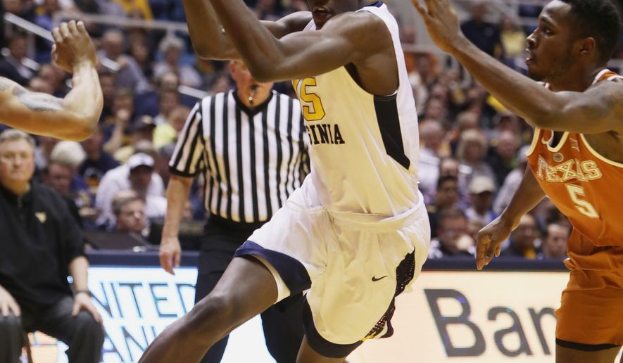 West Virginia forward Lamont West (15) drives to the basket while being guarded by Texas guard Kendal Yancy (5) during the second half of an NCAA college basketball game, Monday, Feb. 20, 2017, in Morgantown, W.Va. (AP Photo/Raymond Thompson)