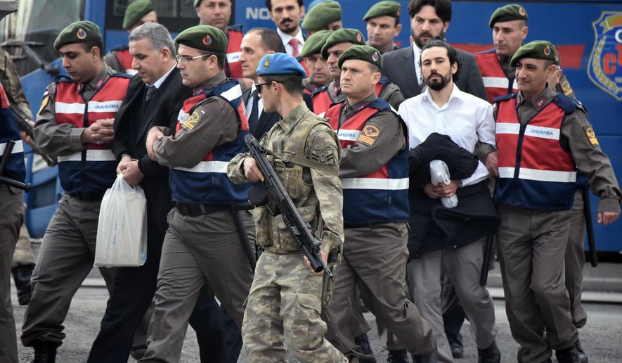 Paramilitary police escort defendants as a trial opened in Mugla, southern Turkey, Monday, Feb. 20, 2017. The trial for 47 people charged with attempting to kill President Recep Tayyip Erdogan on the night of the failed coup, while he was vacationing with his family. The suspects - 37 of them former military personnel - face possible life sentences on charges that include attempted assassination, overthrow of the constitutional order and other crimes against the state during the July 15 coup attempt ( DHA-Depo Photos via AP)