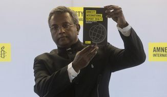 Secretary General of Amnesty International Salil Shetty shows the 2016/2017 Amnesty International report during a press conference, in Paris, Tuesday, Feb. 21, 2017. (AP Photo/Thibault Camus)