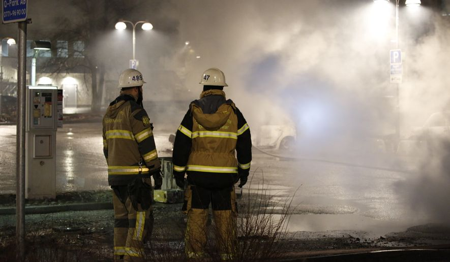 Fire fighters in the suburb Rinkeby outside Stockholm,  Monday Feb. 20, 2017.  Swedish police on Tuesday were investigating a riot that broke out overnight in a predominantly immigrant suburb in Stockholm after officers arrested a suspect on drug charges. The clashes started late Monday when a police car arrested a suspect and people started throwing stones at them. (Christine Olsson / TT via AP)