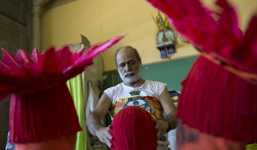 In this Feb. 8, 2017 photo, a man prepares costumes for the upcoming Carnival at the Imperatriz Leopoldinense samba school, in Rio de Janeiro, Brazil. Rio's world famous party is about to kick off amid a prolonged economic crisis that is impacting locals, tourists and a myriad of businesses that depend on the bash for a large part of their annual incomes. (AP Photo/Silvia Izquierdo)