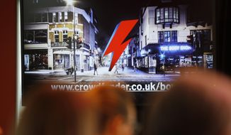 Journalists watch a TV screen that shows the virtual memorial, during a press conference to announce a permanent memorial in Brixton to the late Ziggy Stardust singer David Bowie in London, Tuesday, Feb. 21, 2017.(AP Photo/Frank Augstein)