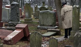 People walk through toppled graves at Chesed Shel Emeth Cemetery in University City, Mo., on Tuesday, Feb. 21, 2017. Authorities in Missouri are investigating after dozens of headstones were tipped over at the Jewish cemetery near St. Louis. (Robert Cohen/St. Louis Post-Dispatch via AP)