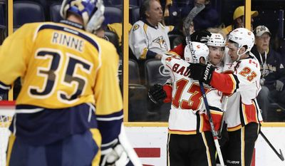 Calgary Flames left wing Micheal Ferland (79) is congratulated by Johnny Gaudreau (13) and Sean Monahan (23) after Ferland scored a goal against Nashville Predators goalie Pekka Rinne (35), of Finland, during the first period of an NHL hockey game Tuesday, Feb. 21, 2017, in Nashville, Tenn. (AP Photo/Mark Humphrey)
