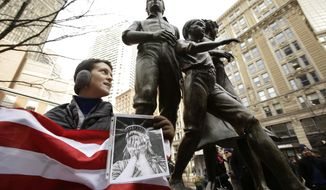 """Molly Hitt, of Boston, displays an American flag while standing in front of a memorial to the Irish potato famine, right, during a rally called """"We Will Persist,"""" Tuesday, Feb. 21, 2017, in Boston. According to organizers the rally was held to send a message to Republicans in Congress and the administration of President Donald Trump that they will continue to press for immigration rights and continued affordable healthcare coverage. (AP Photo/Steven Senne)"""