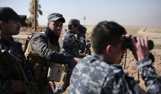 Federal police officers look towards Islamic State group territory as civilians flee the area, in the town of Abu Saif, Iraq, Tuesday, Feb. 21, 2017. A military spokesman says Iraqi forces are consolidating their gains south of Mosul ahead of moving deeper into the city's Islamic State-held western half. The spokesman of the Joint Military Operation Command, Brig. Gen. Yahya Rasool, told The Associated Press that nearly 123 square kilometers -- about 47 square miles -- have been taken south of Mosul since the new push started on Sunday. (AP Photo/Bram Janssen)