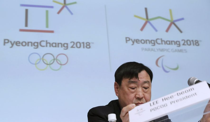 Lee Hee-beom, president and CEO of the Pyeongchang Organizing Committee for the Olympic and Paralympic Winter Games (POCOG), adjusts his name plate prior to a media conference in Sapporo, northern Japan, Tuesday, Feb. 21, 2017. Lee expects the 2018 Olympics to usher in a new era for winter sports in Asia. (AP Photo/Eugene Hoshiko)
