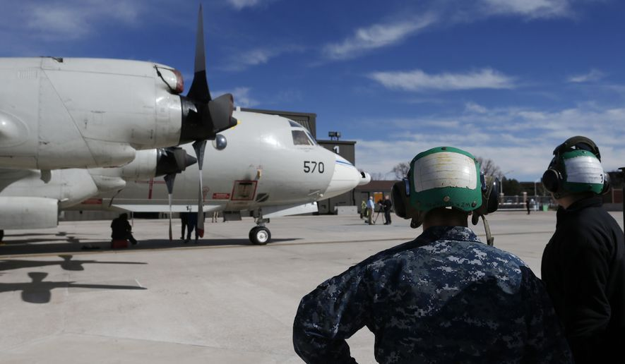 In this Feb. 17, 2017 photo, military ground crew attend to a Navy P-3 Orion aircraft used for a NASA-led experiment called SnowEx, on an airfield at Peterson Air Force Base in Colorado Springs, Colo. Airplanes are scanning the Colorado high country with an array of sensors as scientists search for better ways to measure how much water is locked up in the world's mountain snows. (AP Photo/Brennan Linsley)