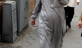 FILE -- In this file photo taken on April 11, 2007, Egyptian cleric Osama Hassan Mustafa Nasr, known as Abu Omar, who was allegedly kidnapped by CIA agents off the streets of an Italian city and taken to Egypt where he said he was tortured, talks on his mobile as he walks at a Cairo street after attending Amnesty International press conference in Cairo, Egypt.  A Portuguese court ordered police to extradite a former CIA agent Sabrina de Sousa to Italy, where she is due to serve a four-year prison sentence after being convicted of involvement in a U.S. program that kidnapped suspects for interrogation, her lawyer said Tuesday, Feb. 22, 2017. De Sousa was among 26 Americans convicted for kidnapping suspect Mustafa Nasr.  (AP Photo/Amr Nabil, File)