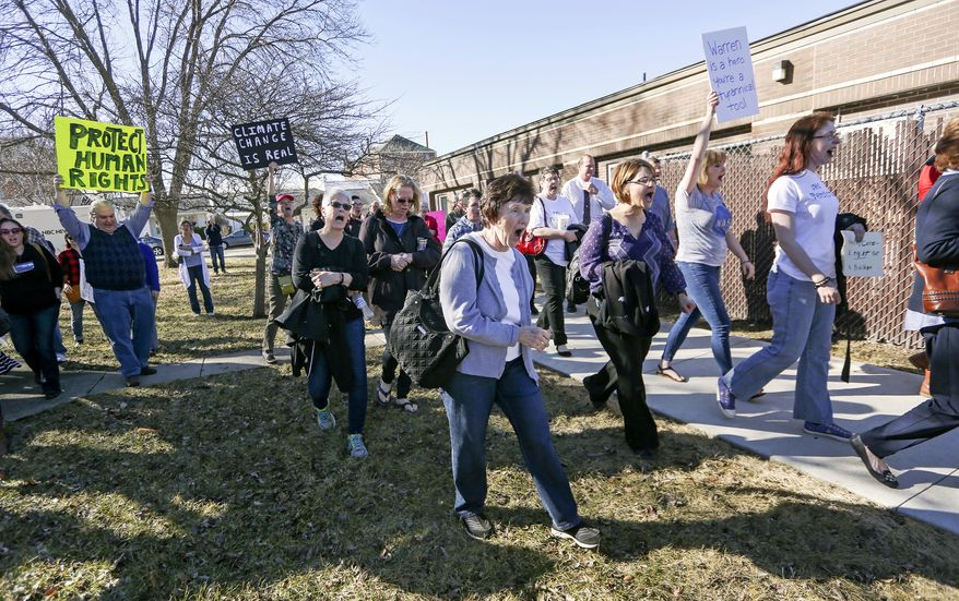 Protesters follow Sen. Joni Ernst, R-Iowa, to her vehicle following a veterans roundtable event at Maquoketa City Hall on Tuesday, Feb. 21, 2017, in Maquoketa, Iowa. Iowa's U.S. senators were met Tuesday with overflow crowds who pointedly questioned them about President Donald Trump's actions during his first month in office and other issues. Although Republican Sens. Charles Grassley and Ernst held meetings in small towns in northern and eastern Iowa, they drew big crowds. (Nicki Kohl/Telegraph Herald via AP)