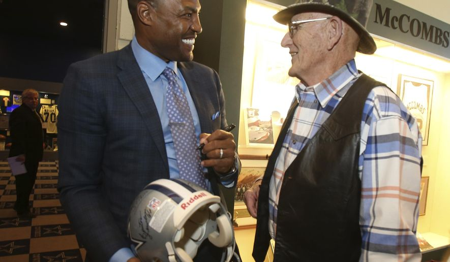 Darren Woodson, left, autographs a helmet of his playing days with the Dallas Cowboys for fan Reggie Reynolds Tuesday Feb. 21, 2017, in Waco, Texas before being inducted into the Texas Sports Hall of Fame class of 2017. (Jerry Larson, Waco Tribune Herald via AP)