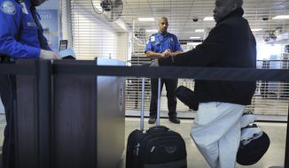 In this Jan. 6, 2010, file photo, a TSA employee being trained in behavioral pattern recognition watches passengers in line at a security checkpoint at Logan International Airport in Boston. (AP Photo/Josh Reynolds, File)