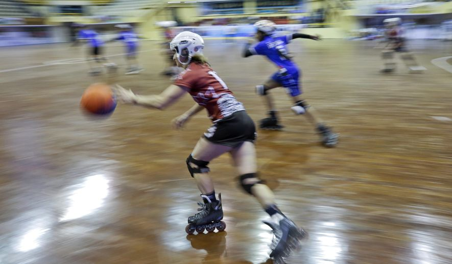 In this Tuesday, Feb. 21, 2017 photo, Aija Apsipe, left, of Latvia dribbles the ball during the 4th Roll Ball World Cup quarterfinal match against India at Shaheed Sohrawardi Indoor Stadium in Dhaka, Bangladesh. Bangladesh hosted the championship for an unusual sport, roll ball, where players on roller skates dribble and pass a basketball-sized ball that they try to throw into a small soccer-type goal. About 750 players from 40 countries around the world took part. Top honors, both for men and women, went to India, where the sport was invented. (AP Photo/A.M. Ahad)