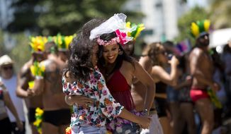 """In this Feb. 19, 2017 photo, a couple dances during the """"If you don't give me....then you lend me"""" Carnival street party on Ipanema beach, in Rio de Janeiro, Brazil. The typical view of Carnival in Brazil is anything goes, with no headdress too big, no outfit too small, no song too ribald, but this year some organizers of the world's best known party are drawing the line at lyrics that are sexist, homophobic or racist. (AP Photo/Silvia Izquierdo)"""