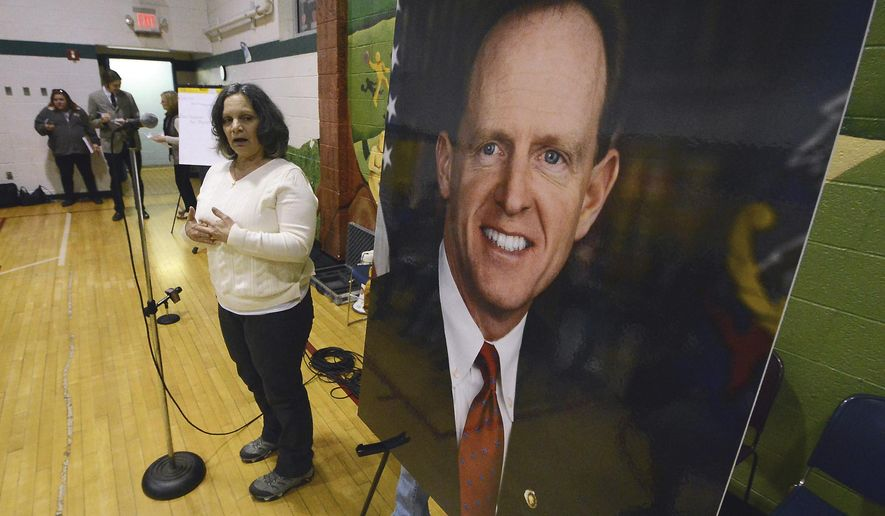 Anna Washick, of Thornhurst, Pa., tells her story regarding health care next to a large photograph of Sen. Pat Toomey, R-Pa., at the United Neighborhood Center in Scranton, Pa., Tuesday, Feb. 21, 2017. Toomey was invited to speak at the town hall, but did not attend. (Butch Comegys/The Times & Tribune via AP)